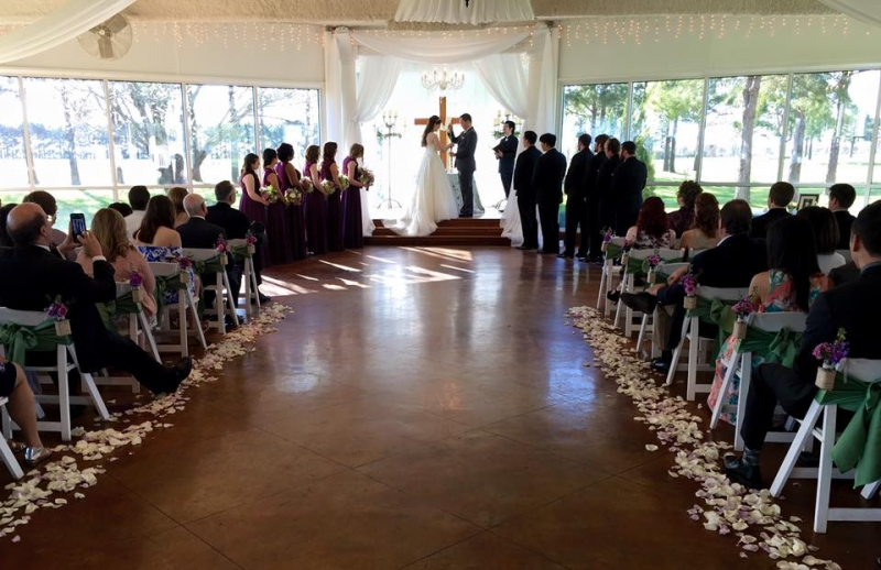 Saying vows at an indoor wedding at House Plantation with purple flower chair decor