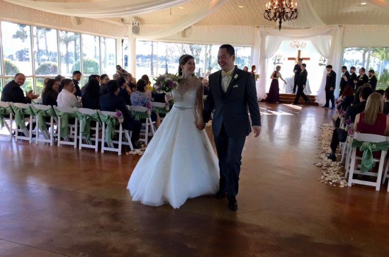 Walking the aisle with white rose petals and green sashed chairs at House Plantation