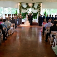 Taking their vows adorned with flowers at an indoor wedding at House Estate