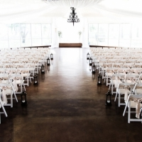 Indoor wedding in Sept with satin bows and lantern markers