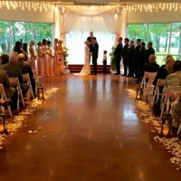 Saying I do at a wedding at House Plantation with rose petals and lantern aisle markers
