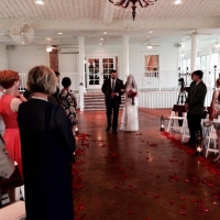 walking down the aisle at House Plantation adorned with red rose petals
