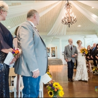 walking the aisle adorned with yellow sunflowers