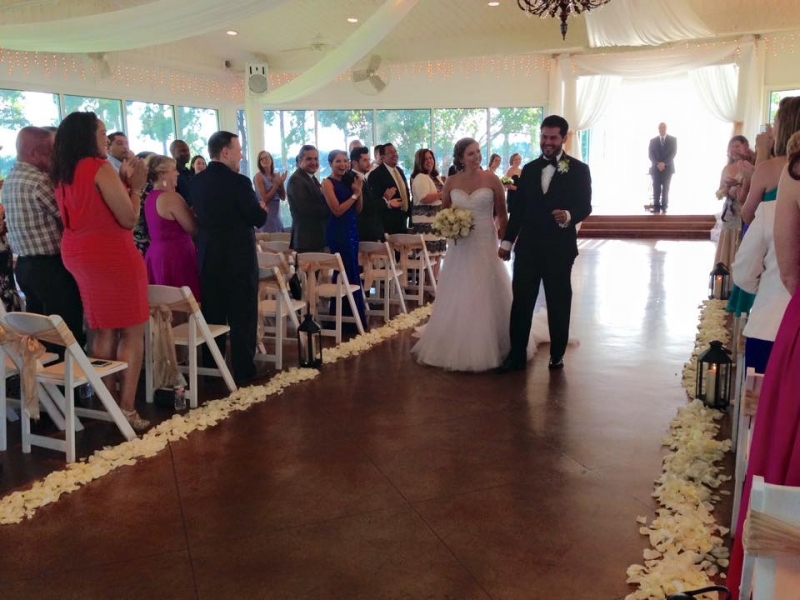 july indoor wedding walking the aisle with white rose petals