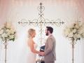 June indoor wedding with cross backdrop