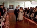 walking the aisle adorned with soft pink rose petals at House Plantation