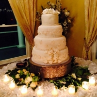 4 tiered soft white wedding cake with edible flowers