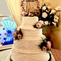 4 tiered white wedding cake at a Katy venue with soft pink flowers
