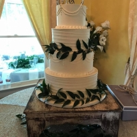 4 tiered white wedding cake with greenery at House Estate