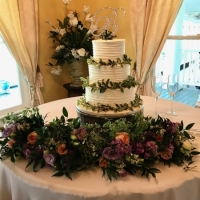 White wedding cake in Houston with flowers and greenery