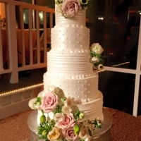 Roses and flowers on a five tiered wedding cake at House  Estate