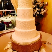 sleek 4 tiered white layered cake with white rose petals