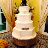 Four tiered elegant white wedding cake with neat topper