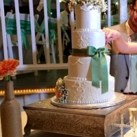elegant four tiered cake with green ribbon