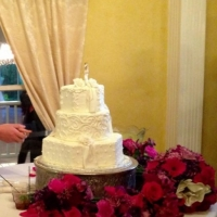 wedding cake surrounded by flowers in beautiful shades of pink