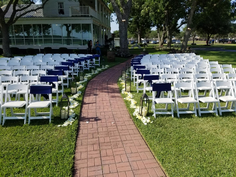 outdoor wedding aligned with lanterns and rose petals in Houston