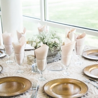 Reception table with light pinks, babies breath and gold buffers