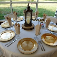 table settings with gold chargers and lantern centerpieces