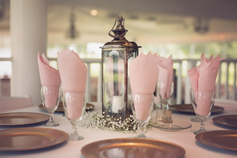 reception table with candles and lanterns and soft pink hues