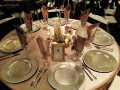 reception table with simple but elegant centerpieces and silver chargers