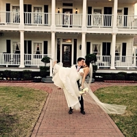 bride and groom poses front of House Plantation