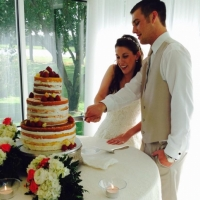 cutting the cake in June with a manicured outdoor view